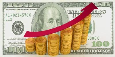 Стопки монет в виде дигарммы на фоне доллара