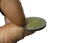монетка в 2 евро зажата между двумя пальцами