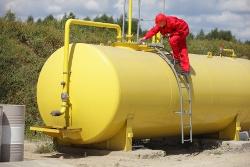 рабочий возле желтой бочки с нефтью